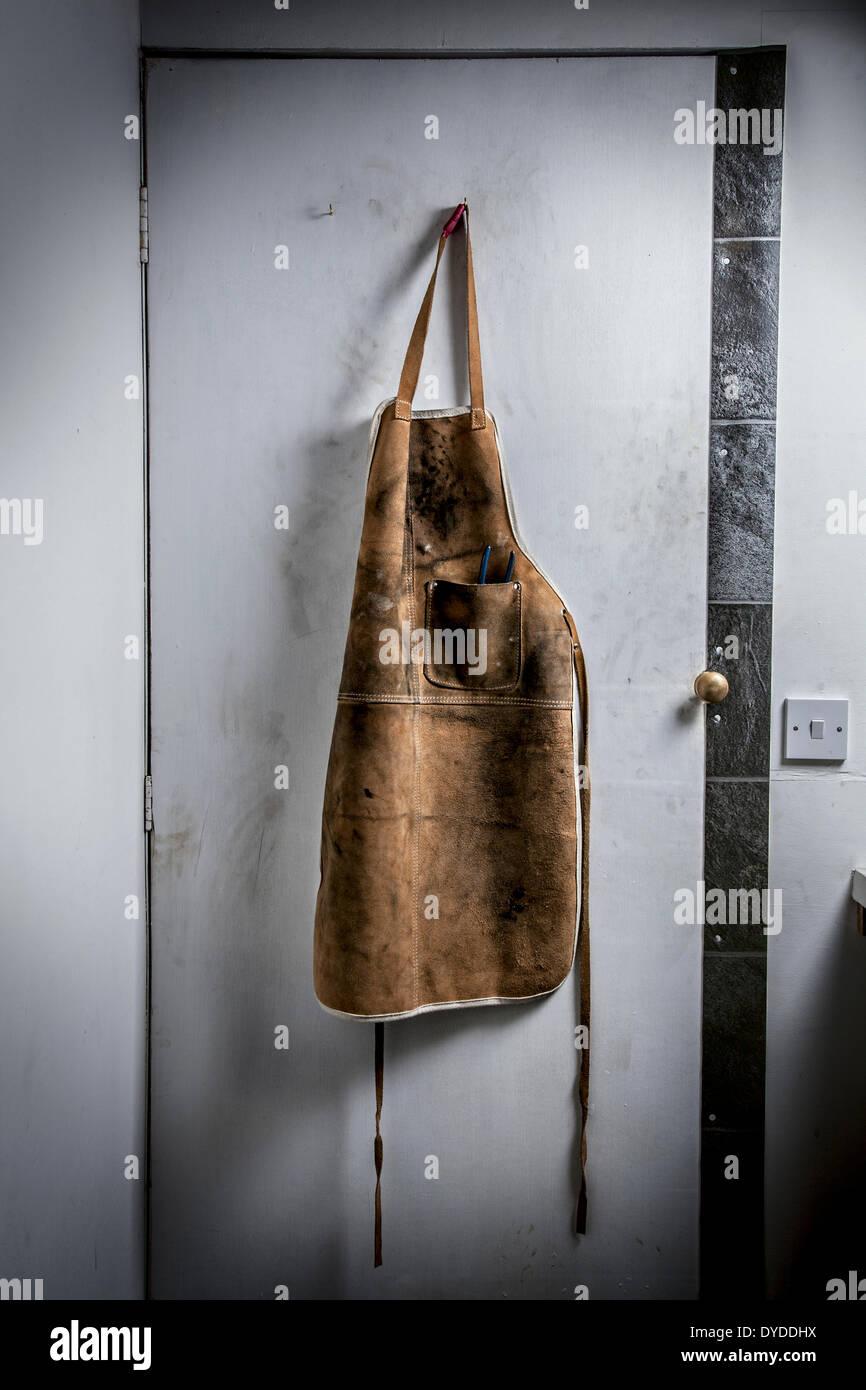 Leather workshop apron hanging on a workshop door. - Stock Image