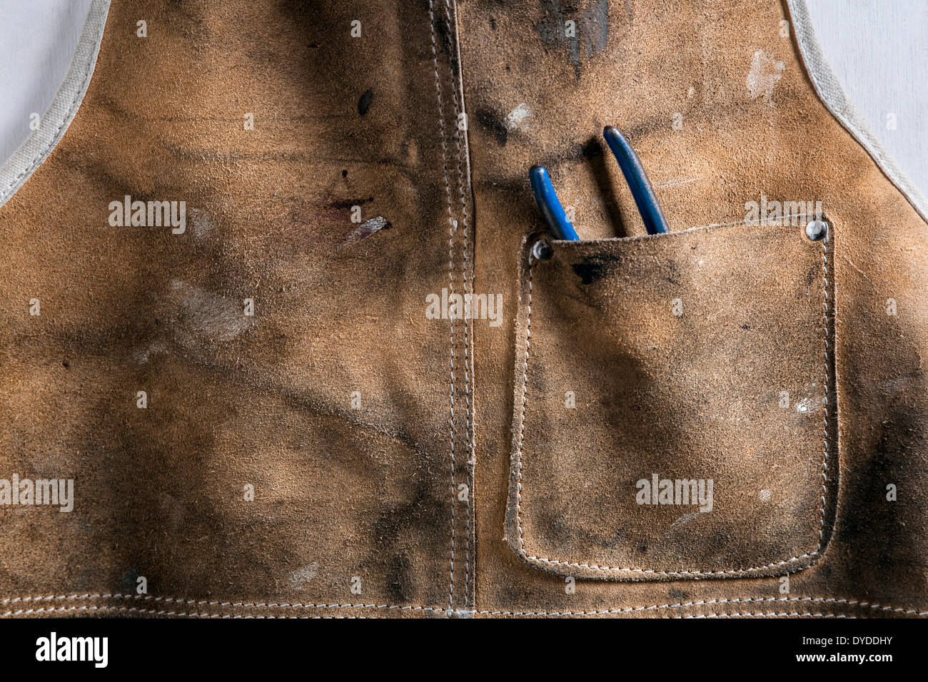 Leather workshop apron with pliers in the pocket. - Stock Image