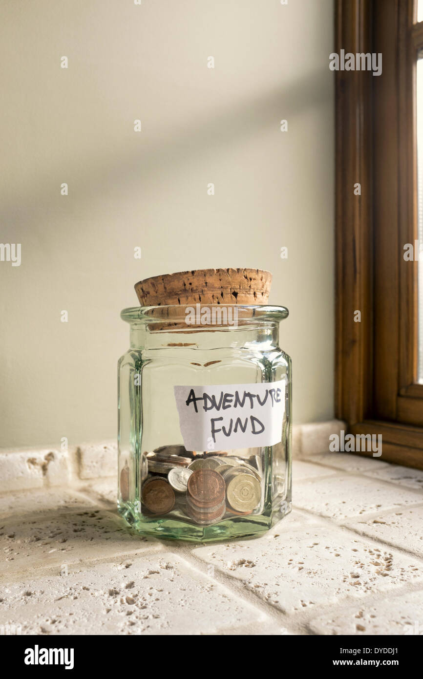 Glass jar labelled Adventure Fund containing loose change. - Stock Image