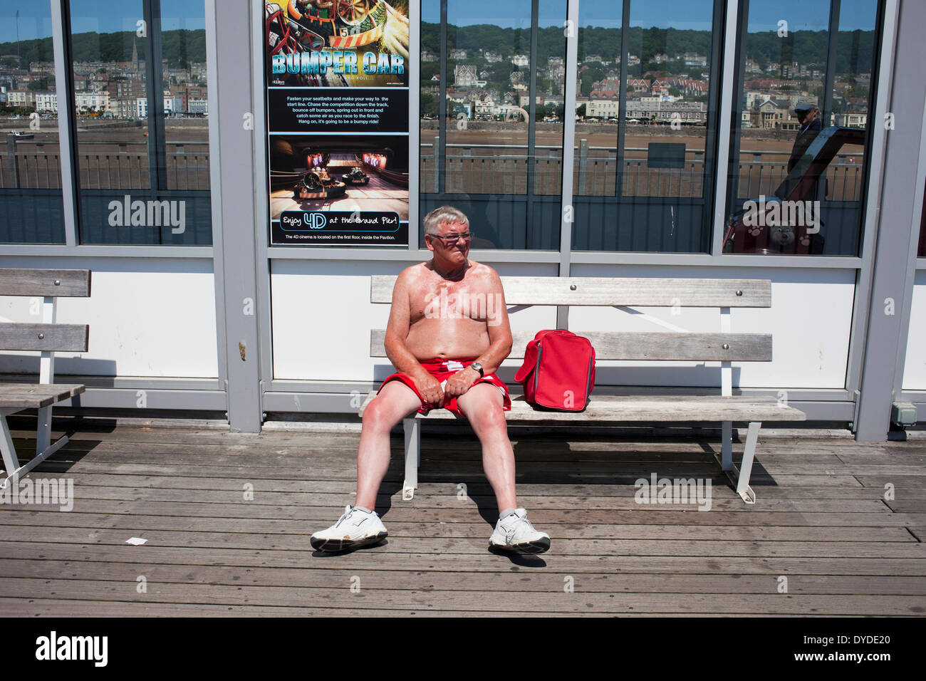 Man with a red short and red bag on Weston Super Mare pier. - Stock Image