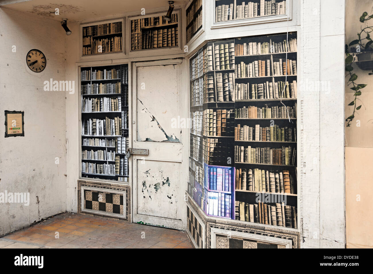 A empty shop with covered windows in the style of book shelves. - Stock Image