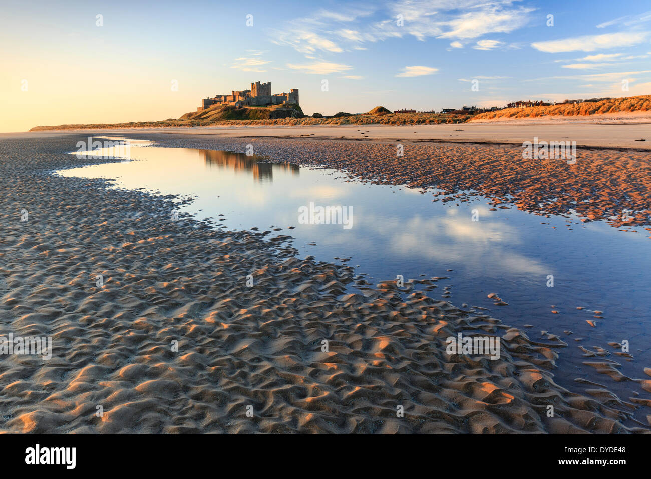 Bamburgh Castle reflected in a tidal pool in early morning sunlight. - Stock Image
