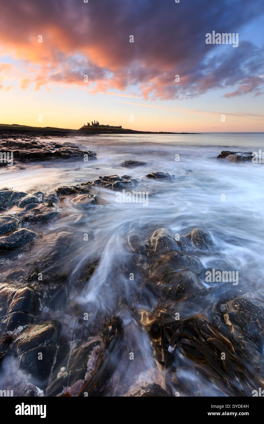 Sunset over Dunstanburgh Castle with waves breaking over the rocks in the foreground. - Stock Image