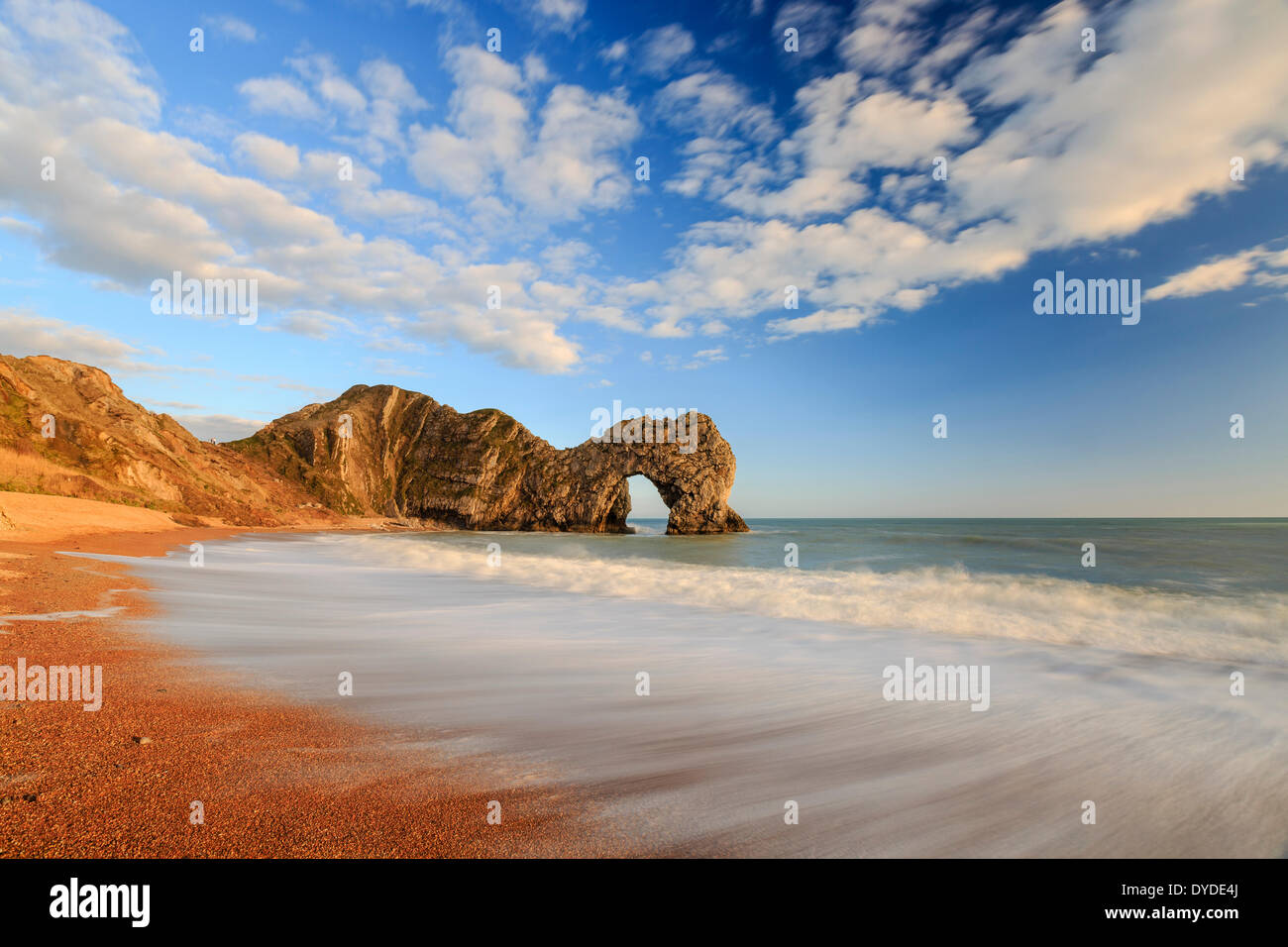 The natural Rock Arch of Durdle Door lit by the evening sun. - Stock Image