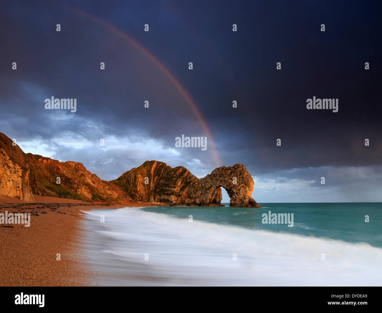 A rainbow over Durdle Door in Dorset. - Stock Image