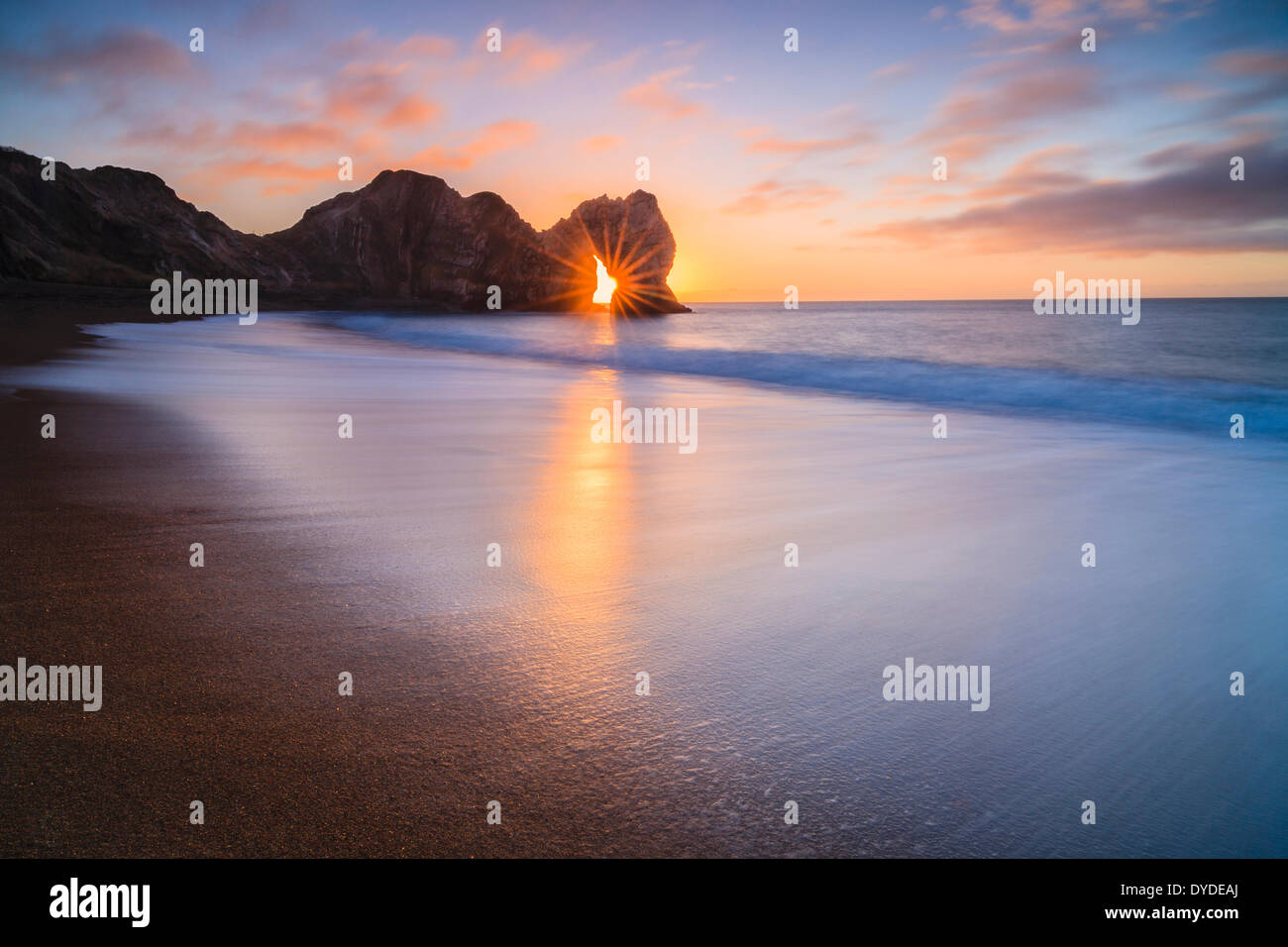 The sun rising through the arch at Durdle Door. - Stock Image