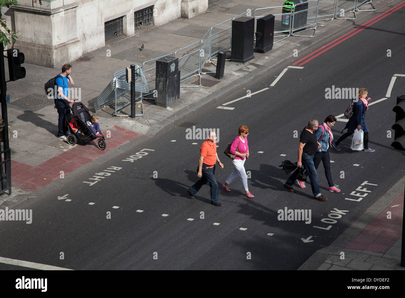 Pedestrians crossing traffic light controlled road crossing. - Stock Image