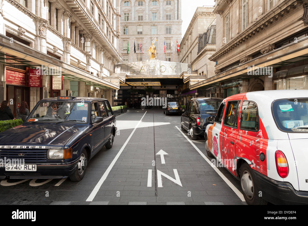 Taxis parked outside the main entrance to Savoy Hotel in the Strand in London. - Stock Image