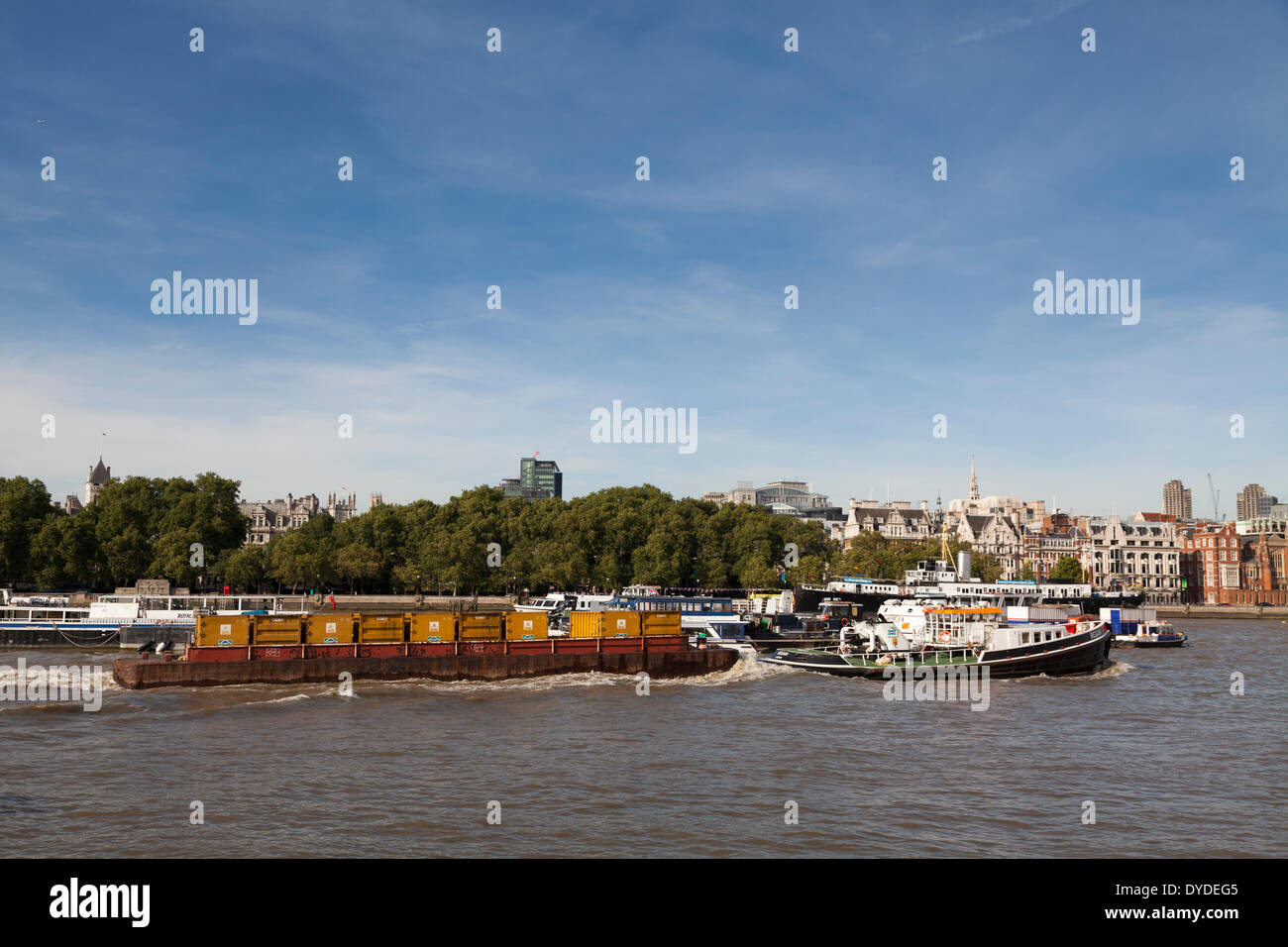 Transport barge of containers being towed down the River Thames. - Stock Image