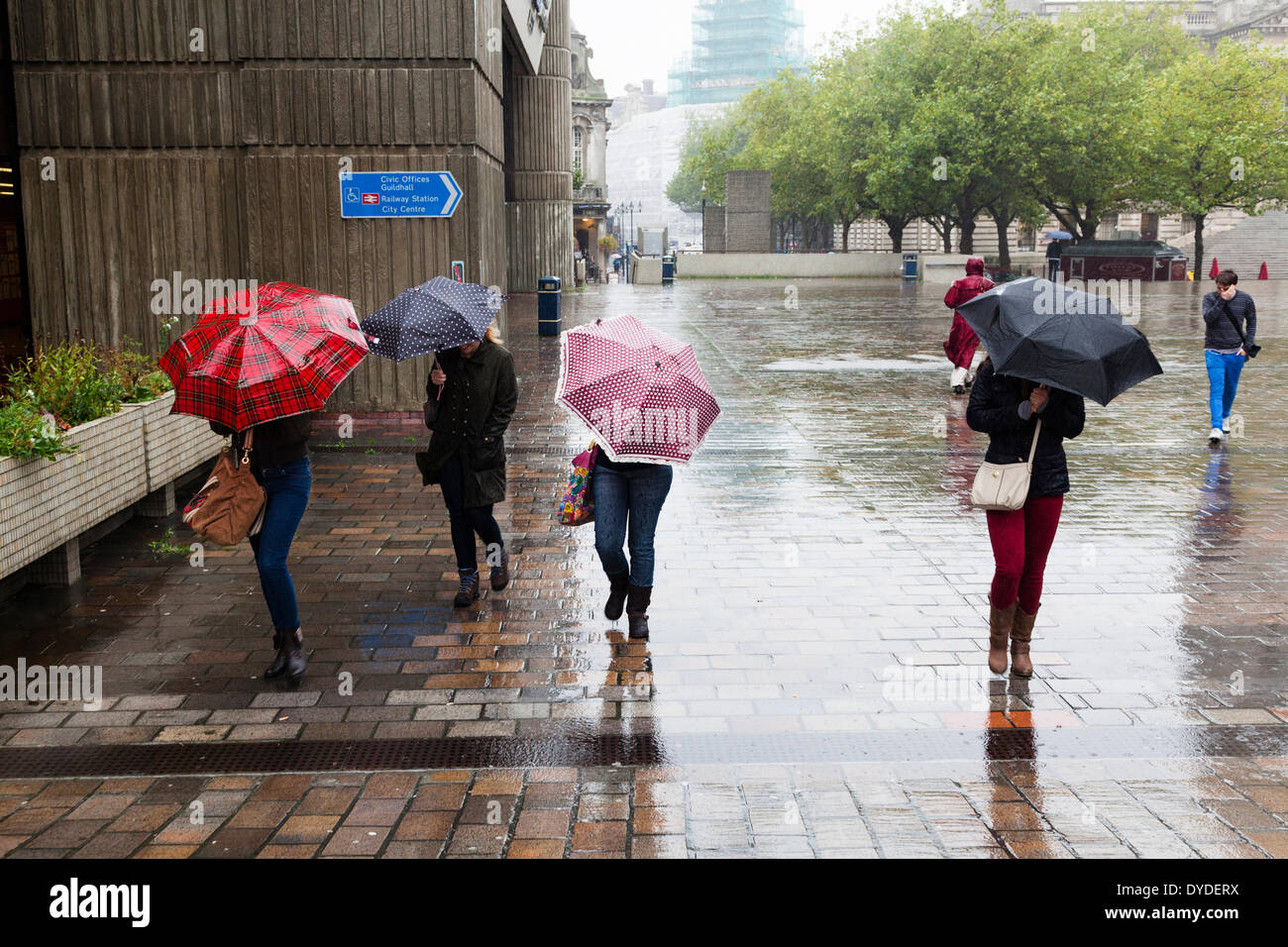 Four women with umbrellas with heads down against the wind and rain. - Stock Image