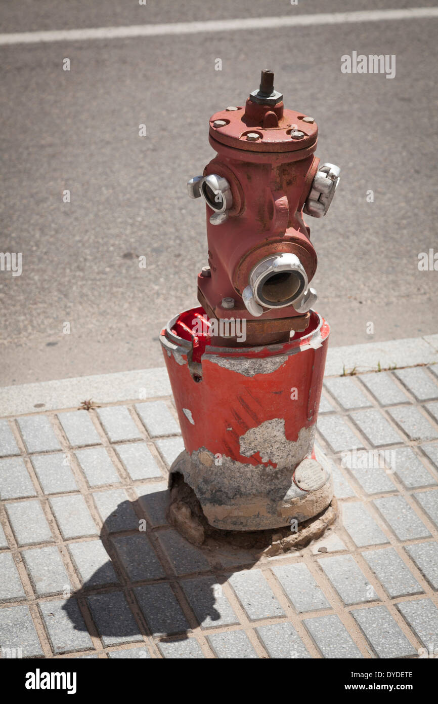 Spanish street fire hydrant with broken concrete protection. - Stock Image