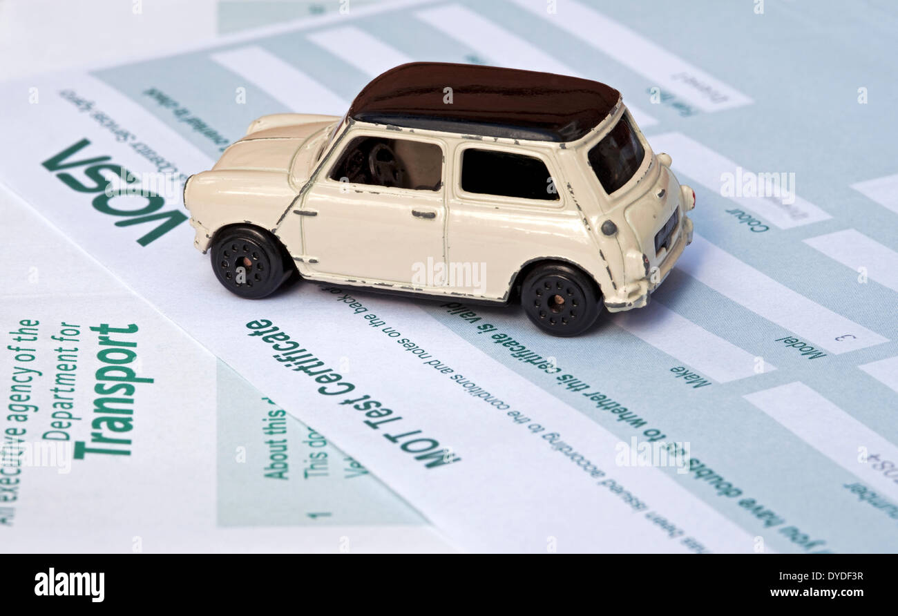 Mini Cooper toy car on an MOT Test Certificate. - Stock Image