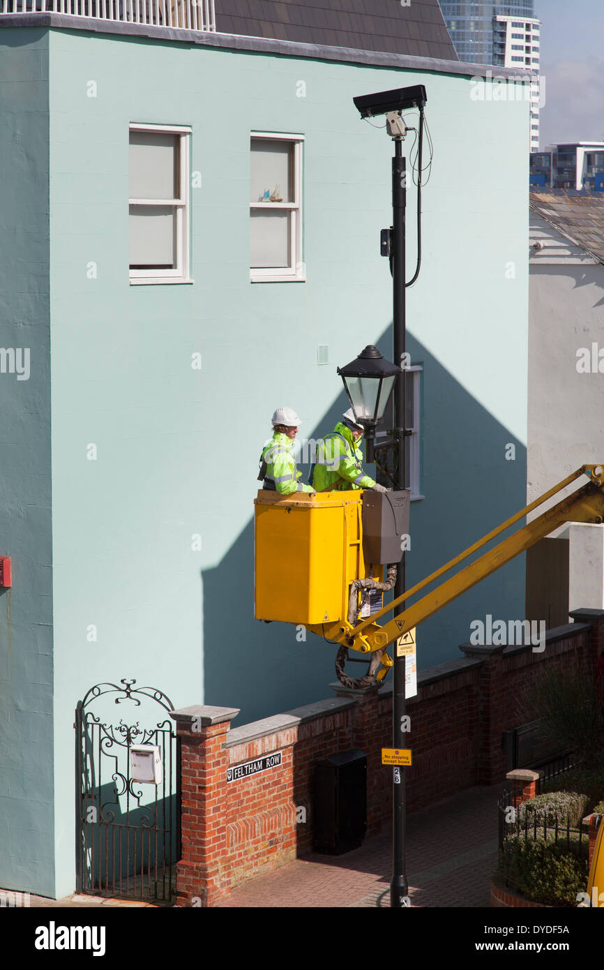 Street furniture maintenance workers using a cherry picker van to maintain street lights. - Stock Image