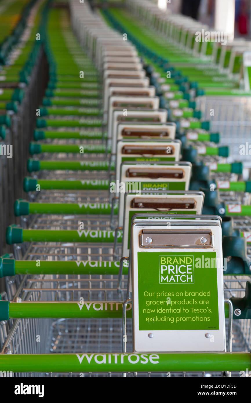 Row of Waitrose supermarket trolleys displaying brand price match slogan. - Stock Image