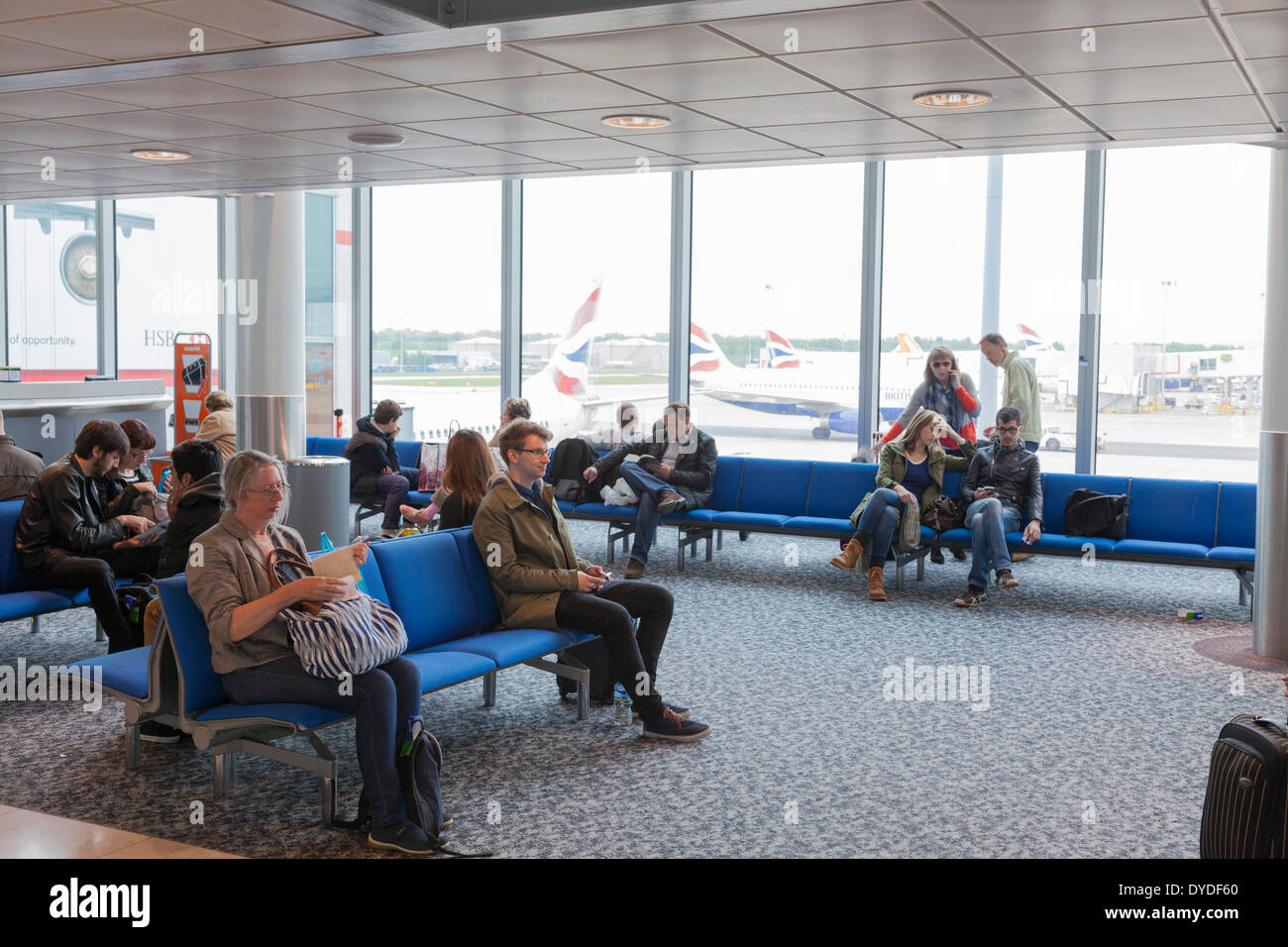 Passengers waiting in airport departure lounge at Gatwick Airport. - Stock Image