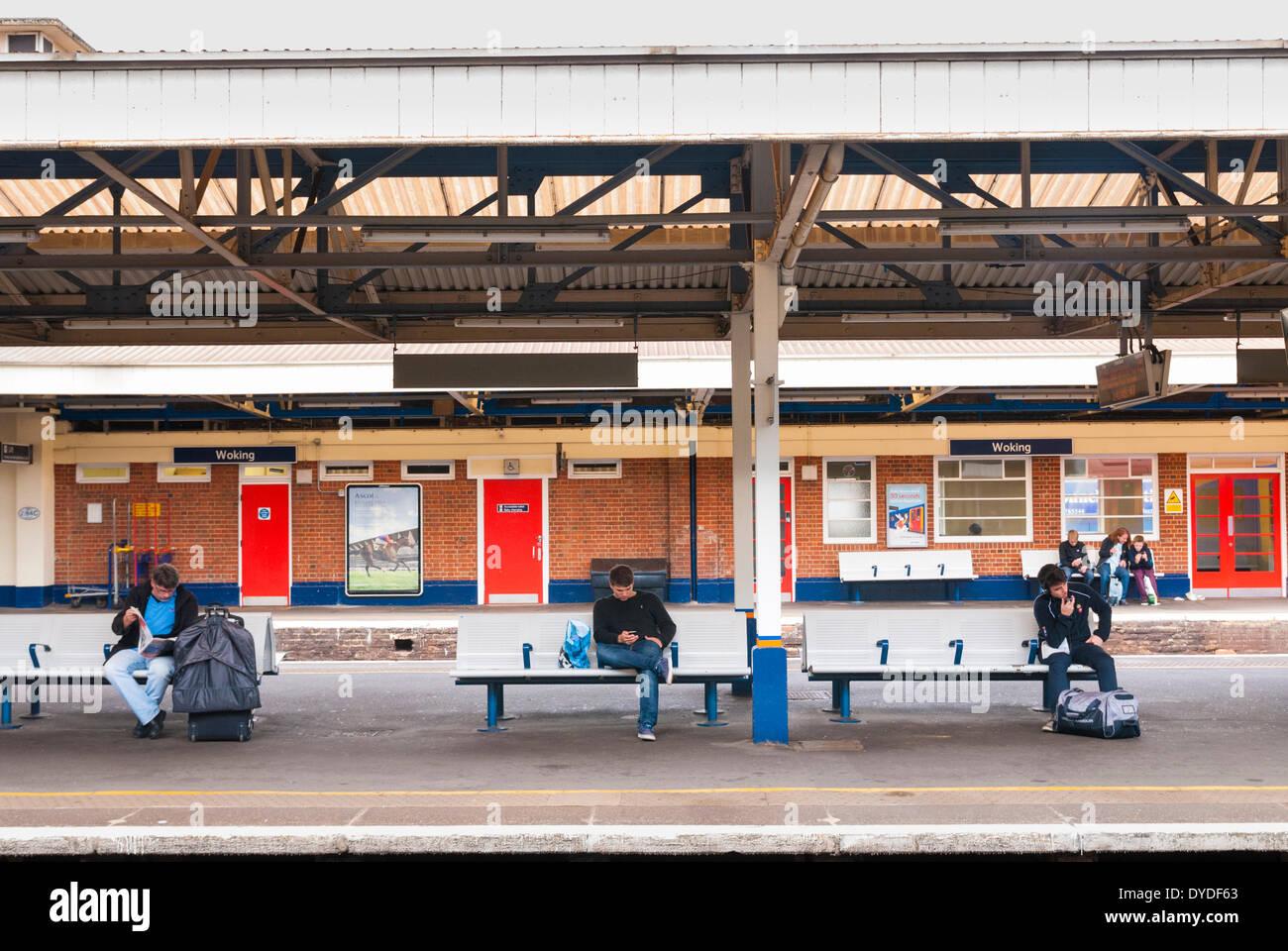 Passengers on platform benches waiting at Woking Station. - Stock Image