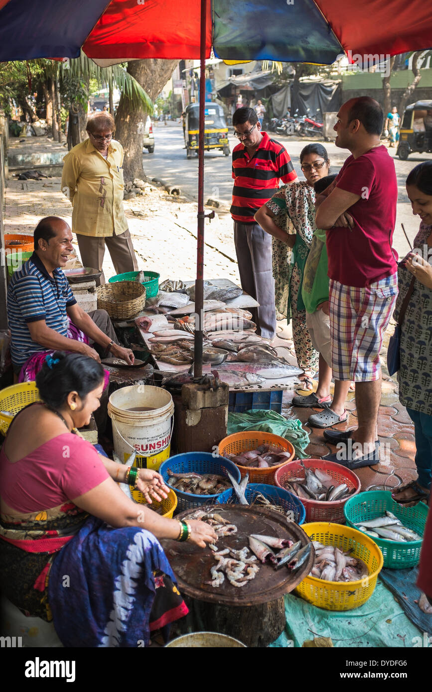 A fishmonger shares a joke with shoppers at his roadside stall. Stock Photo