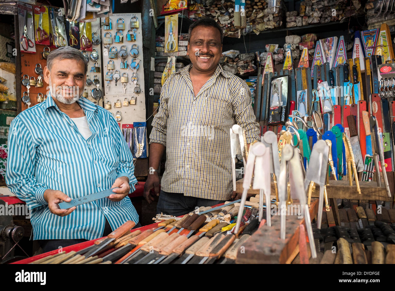 Two men in their shop specialising in metallic items including locks and knives and nutcrackers. - Stock Image