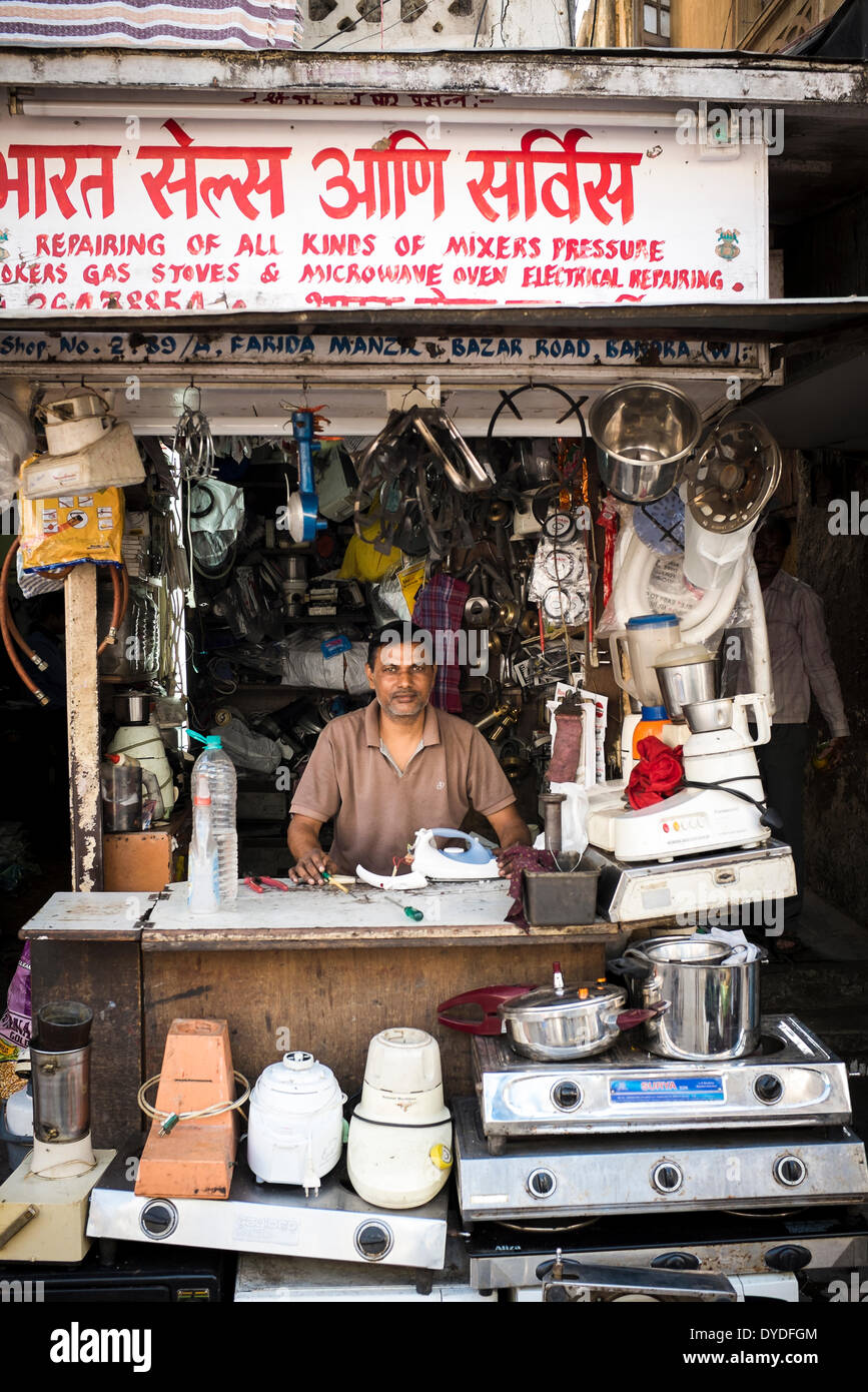 A man behind the counter of his shop specialising in repairs of gas and electrical kitchen appliances. Stock Photo