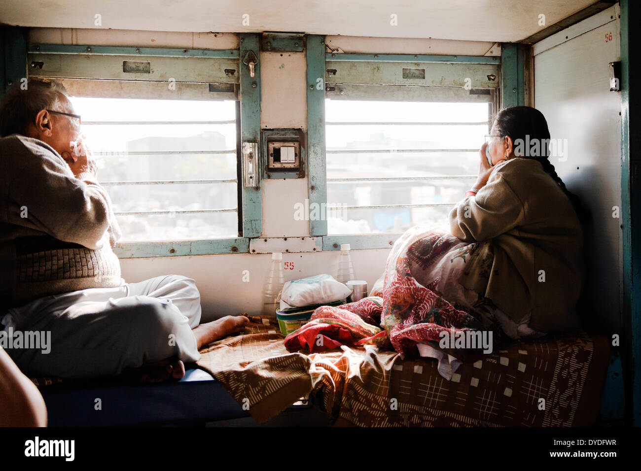 An elderly couple on the train covering their noses due to the smell from a nearby slum. - Stock Image