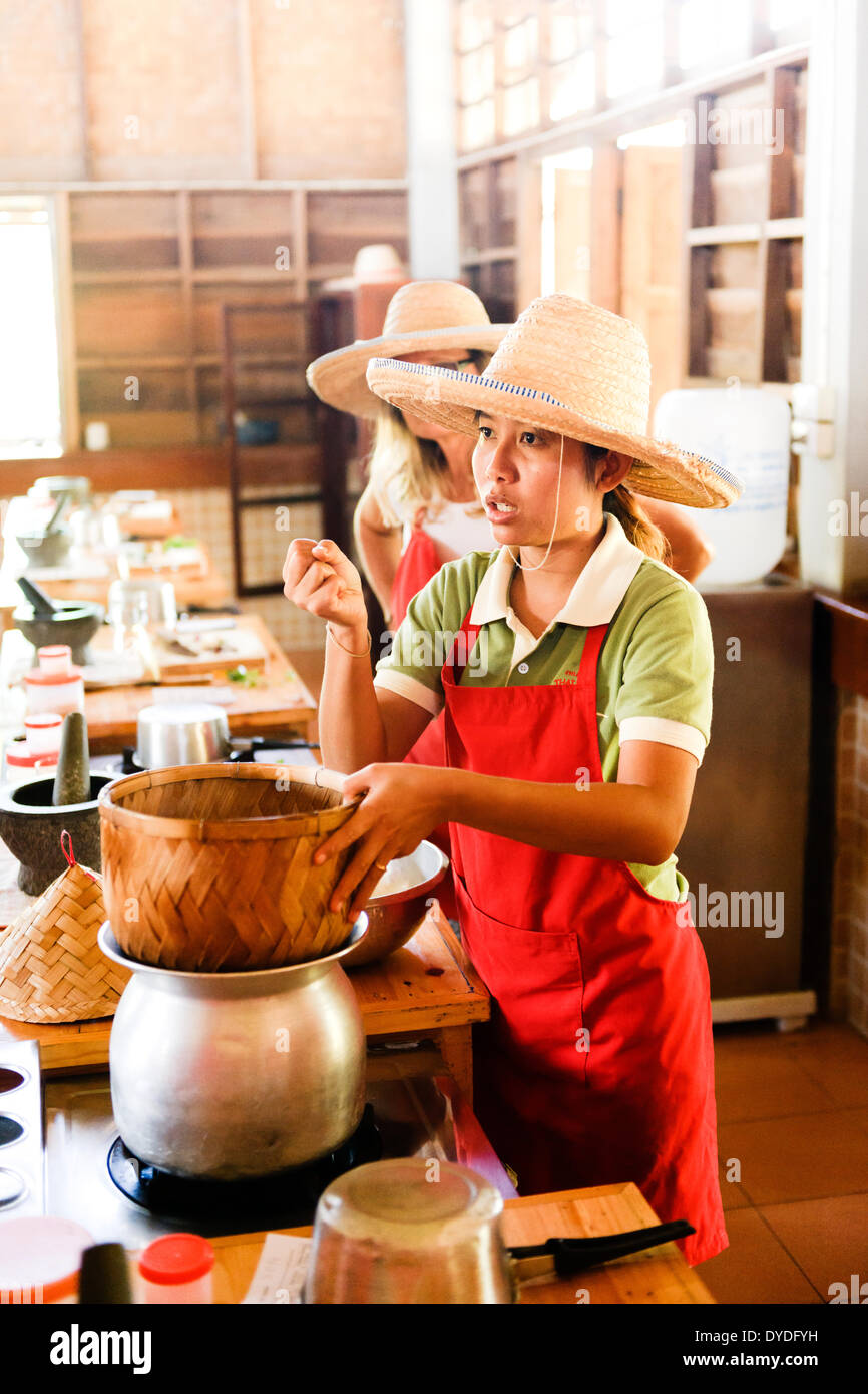 A tutor instructing on how to make Sticky Rice at the Thai Farm Cooking School in Chiang Mai in Thailand. - Stock Image