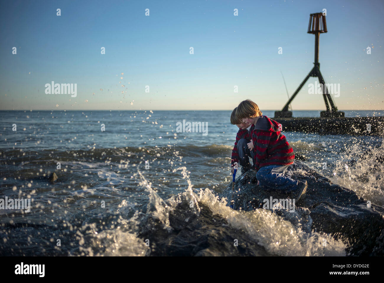 Two boys playing on the rocks at Eastbourne. - Stock Image