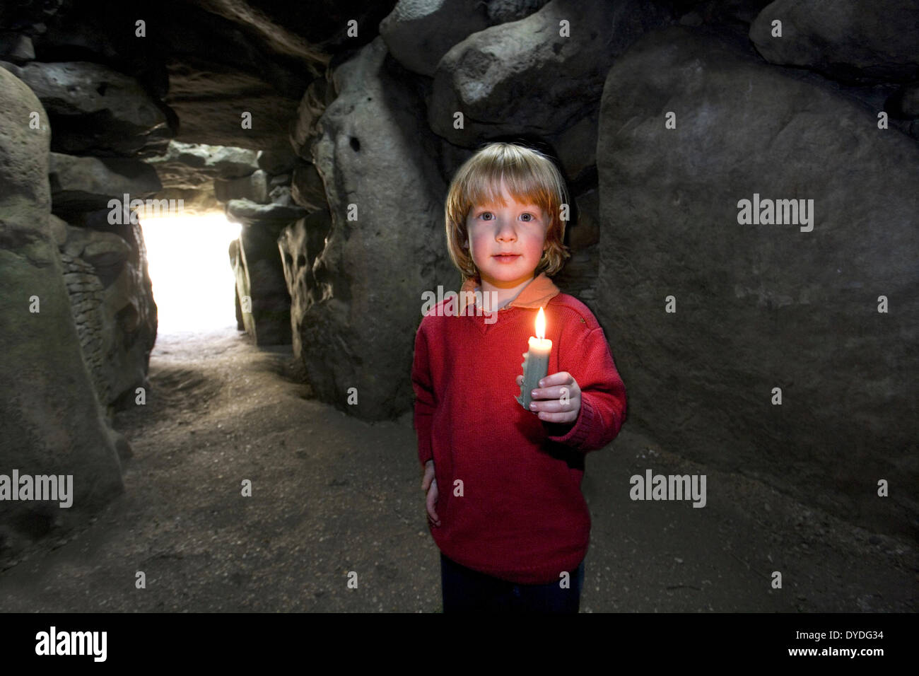 A four year old boy explores West Kennet burial chamber with a candle. - Stock Image