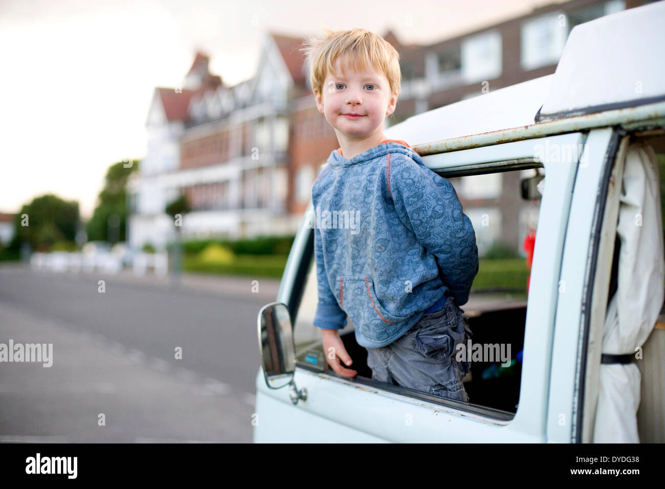 A young boy looks out of his VW bus at the sea side. - Stock Image