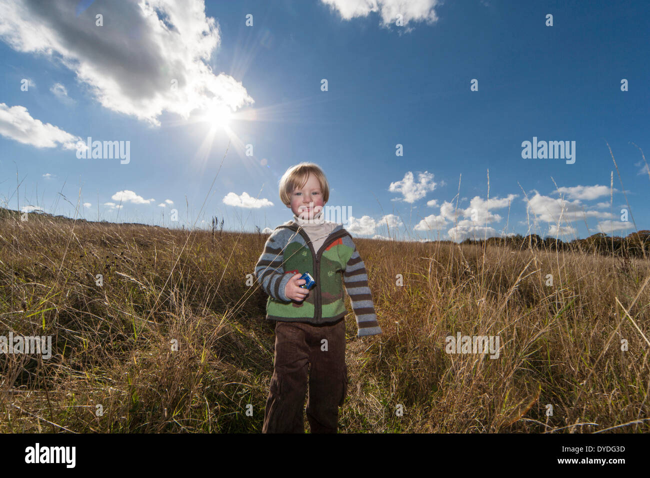 A two year old boy running in the countryside on a sunny day. - Stock Image