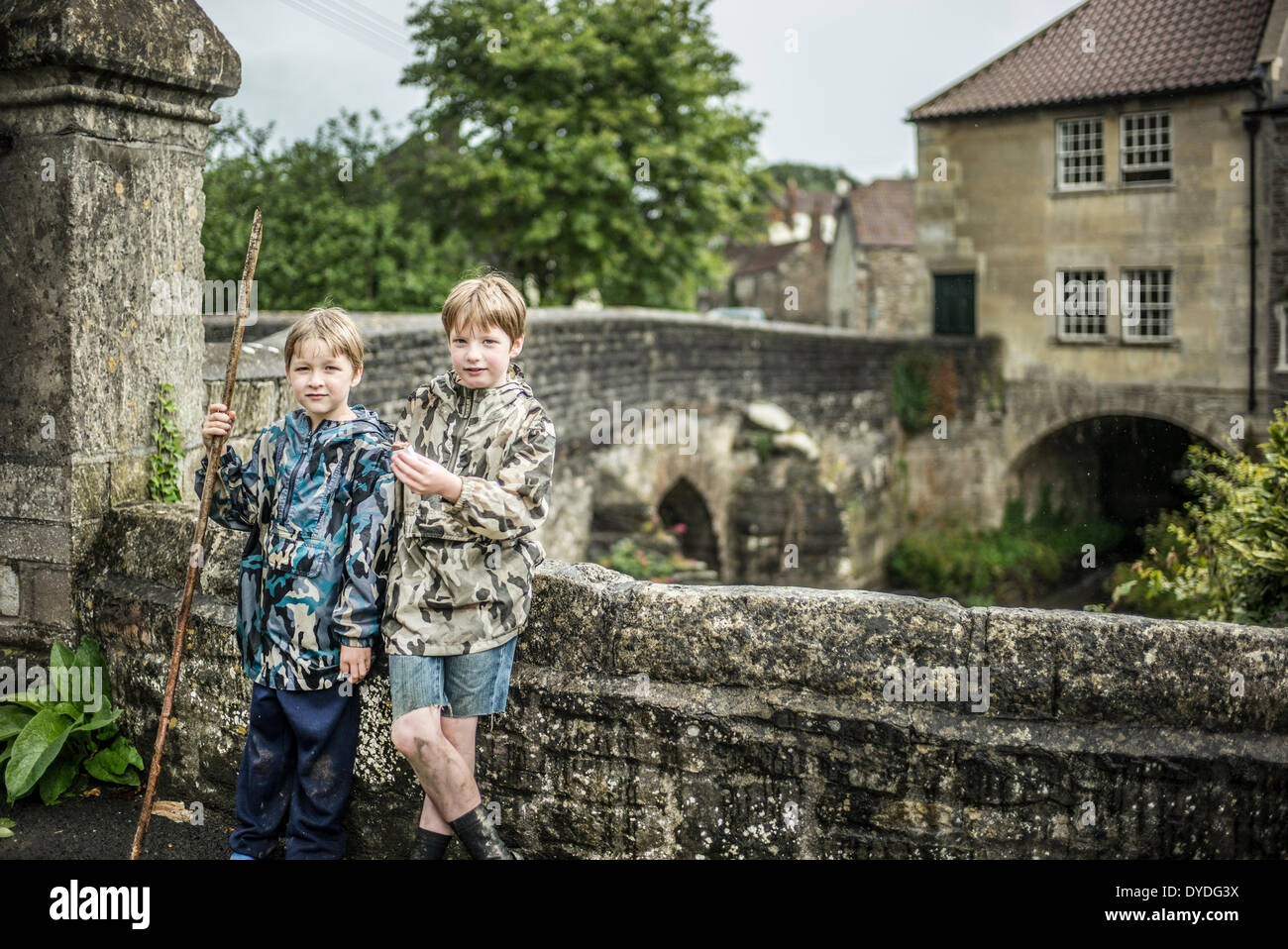 Two brothers stand next to the river Chew at Pensford Bridge in Somerset. Stock Photo