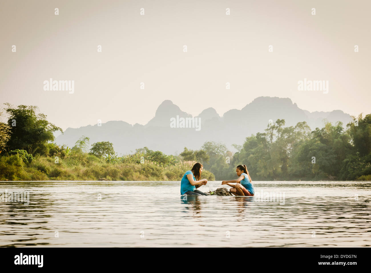 Some local kids enjoying their food on some rocks in the middle of the Nam Song river in Vang Vieng. Stock Photo