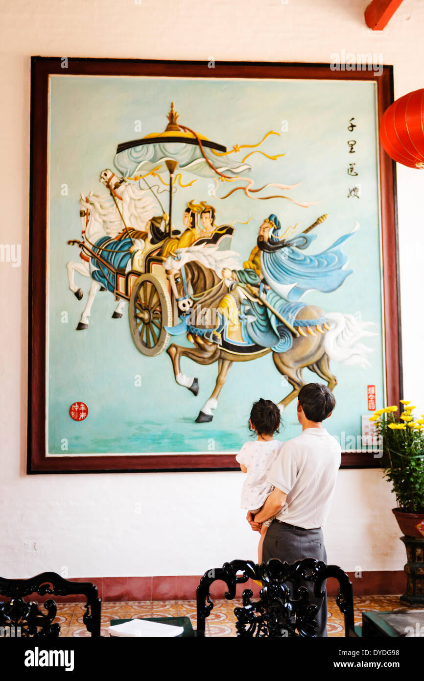 A father and daughter admiring a painting in the Cantonese Assembly Hall at Hoi An. - Stock Image