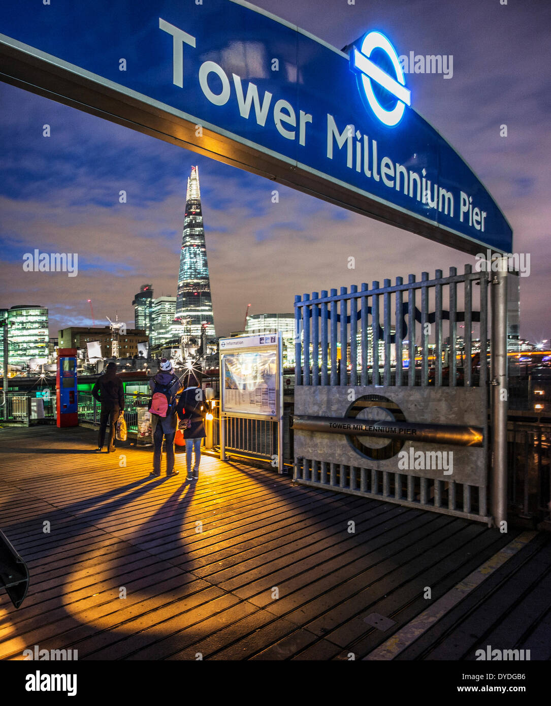 People looking up at The Shard at night from the Tower Millennium Pier. - Stock Image