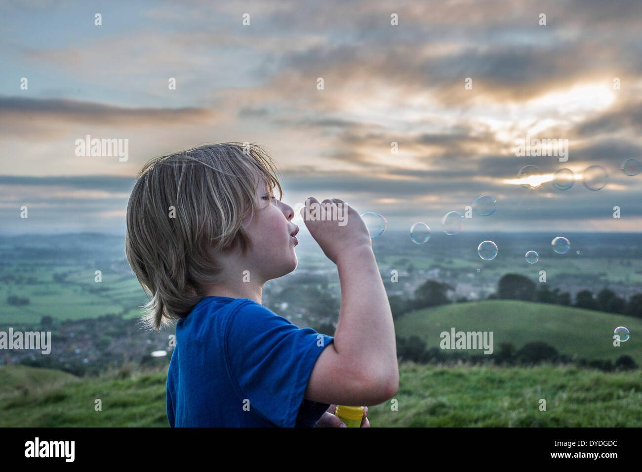 A boy blowing bubbles on Glastonbury Tor. - Stock Image