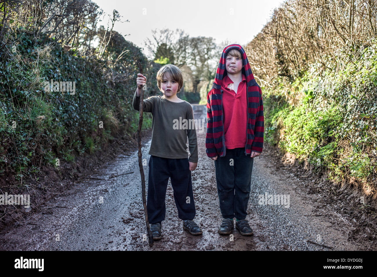 Two boys in a muddy lane. - Stock Image