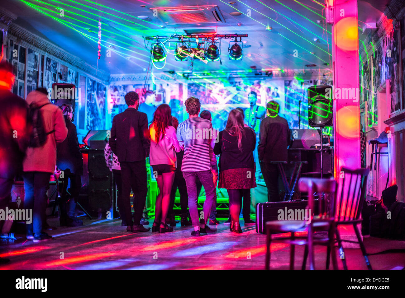 Watching a live performance in a small bar. - Stock Image