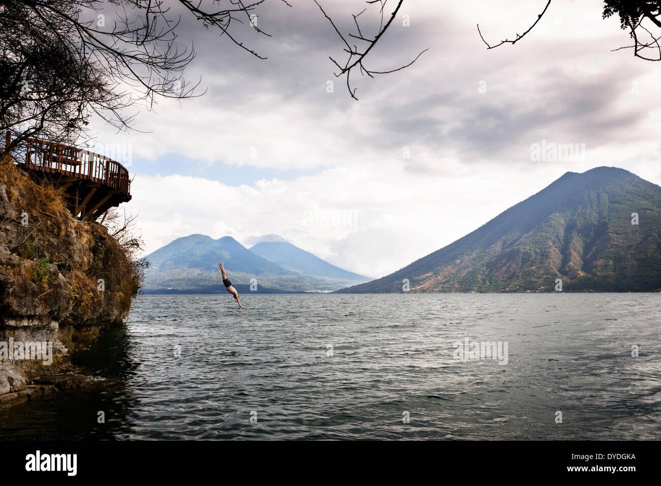 Diving off a platform into Lake Atitlan. - Stock Image
