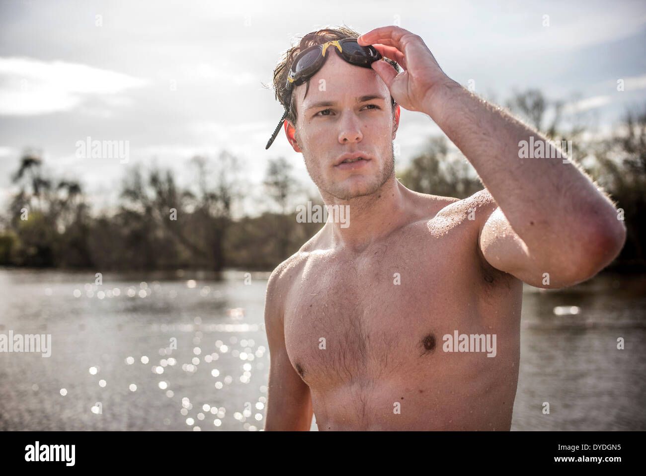 A young man in swimming trunks next to spring fresh water ponds. - Stock Image