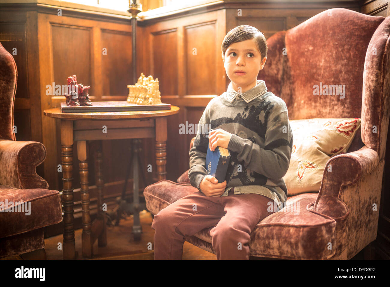 A young boy sitting with a book in Thornbury Castle. - Stock Image