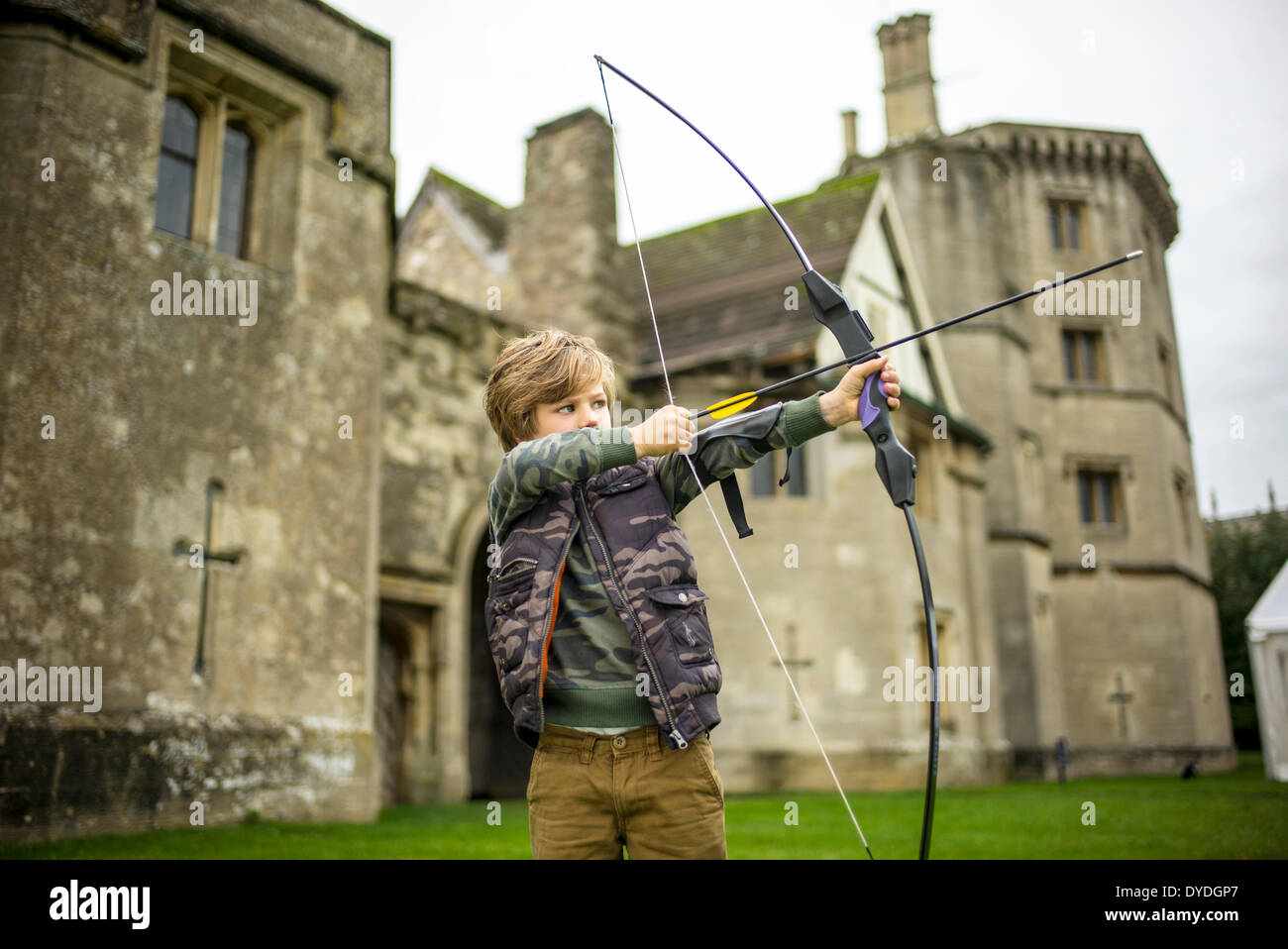 A young boy in Thornbury Castle garden playing archery. - Stock Image