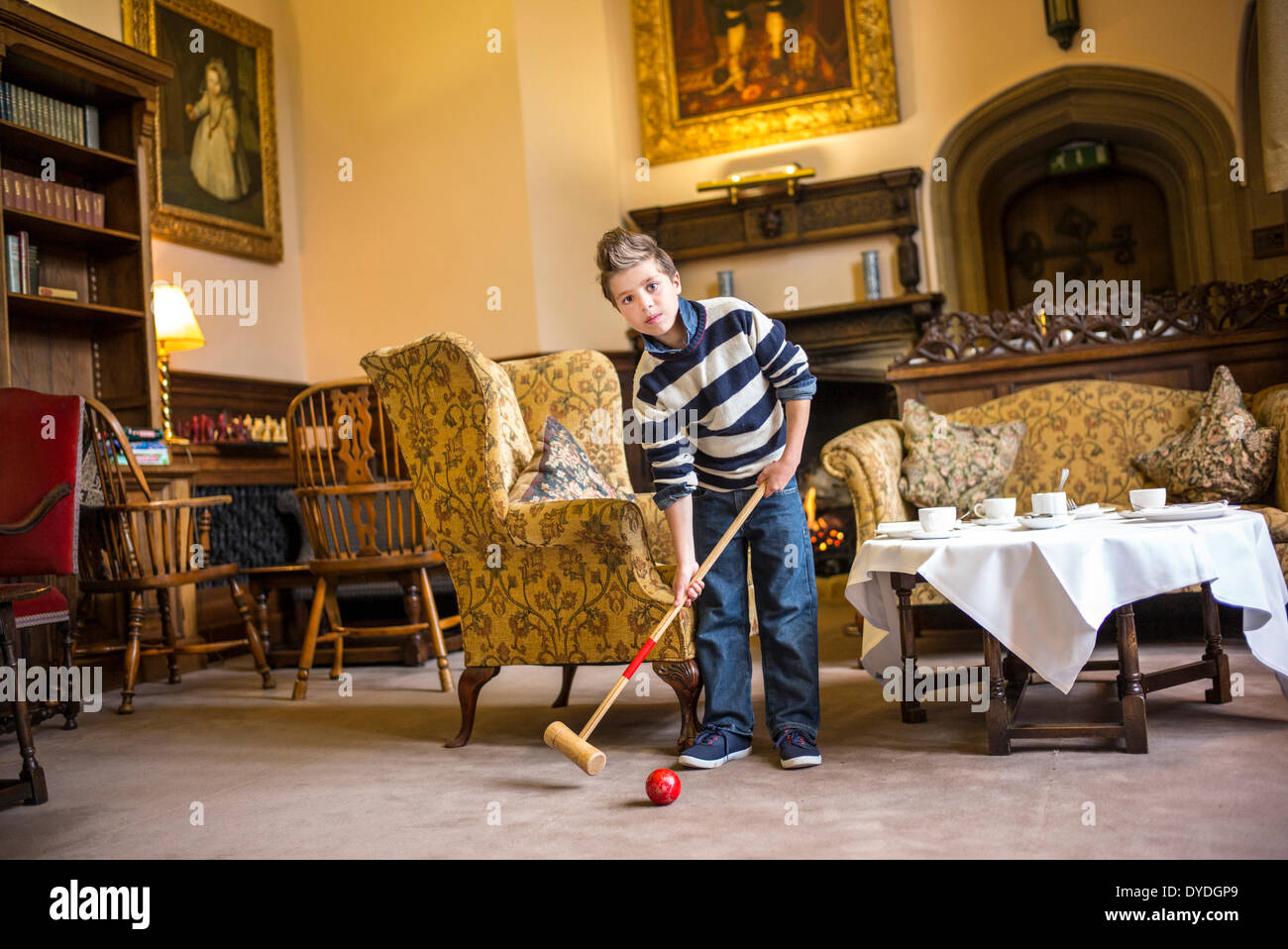 A boy plays croquet in the house at Thornbury Castle. - Stock Image