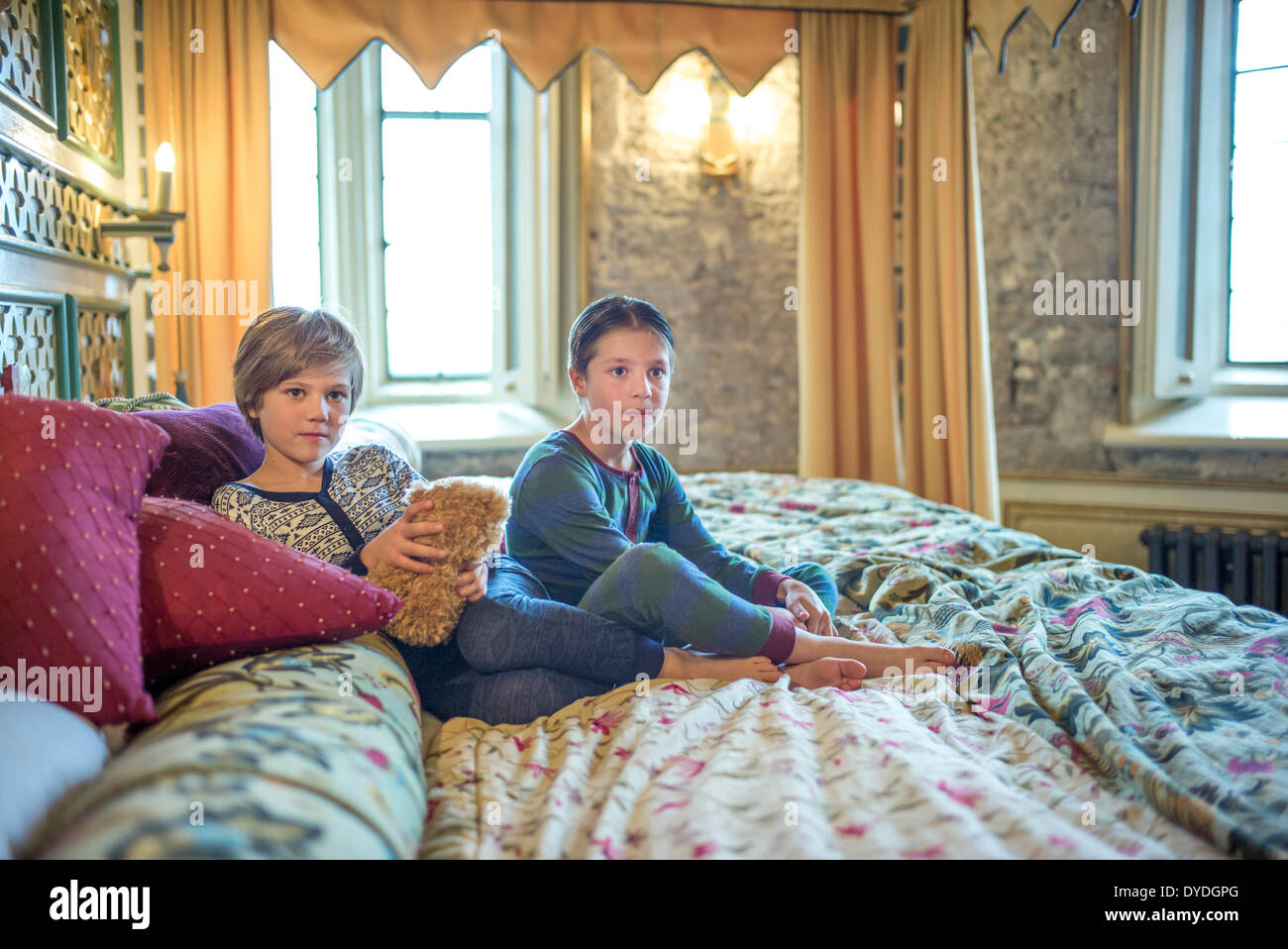 Two boys in onesies on the biggest hotel bed in Europe at Thornbury Castle. - Stock Image