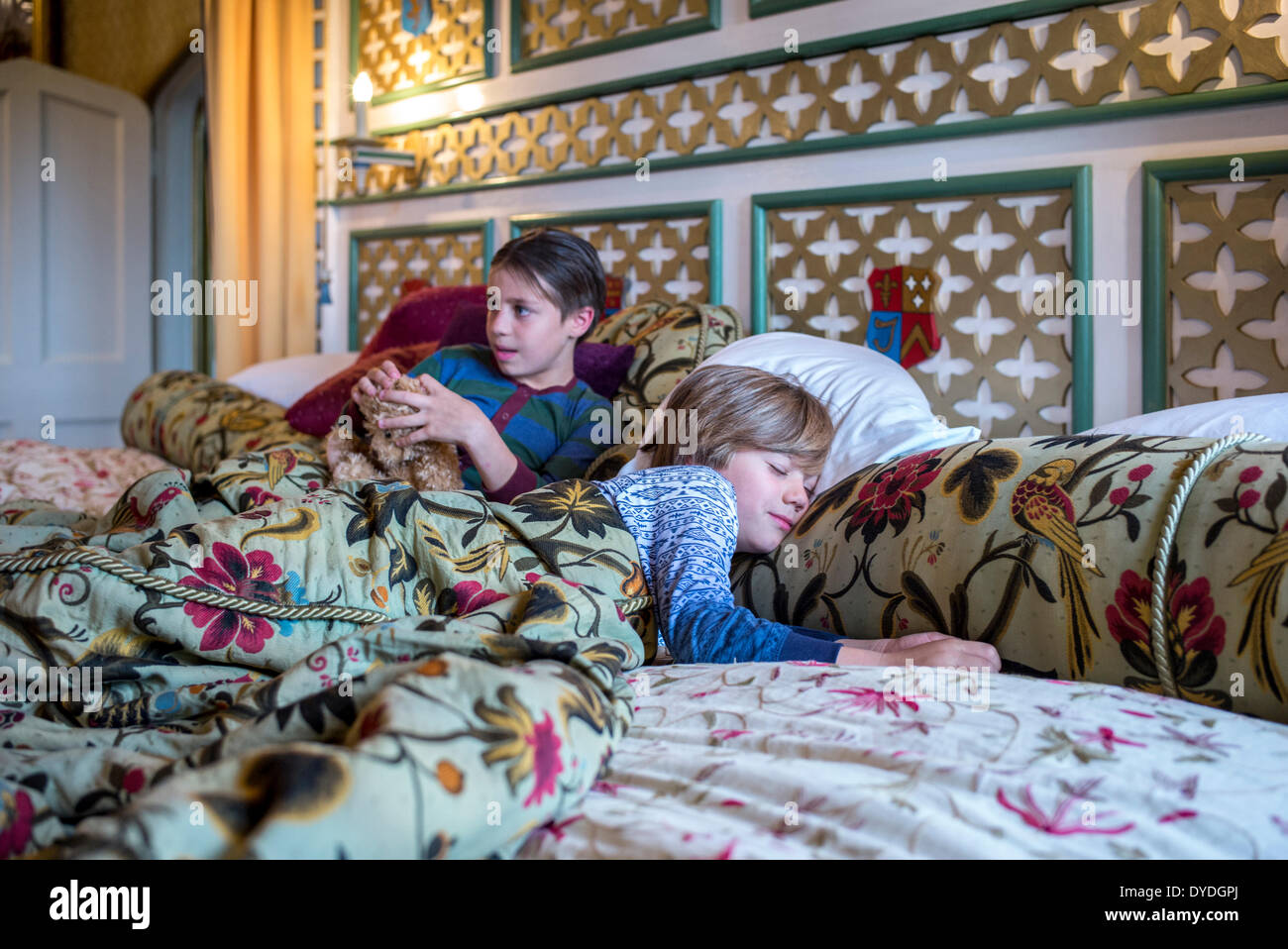 Two boys  in onesies in the biggest hotel bed in Europe at Thornbury Castle. - Stock Image