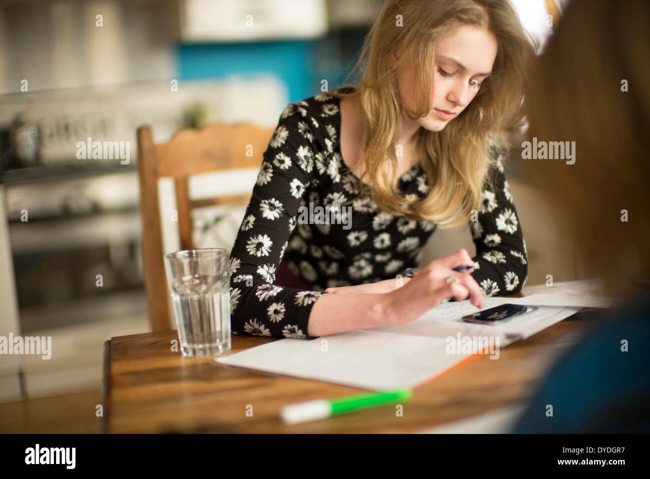 A 16 year old girl doing math homework on the kitchen table. - Stock Image