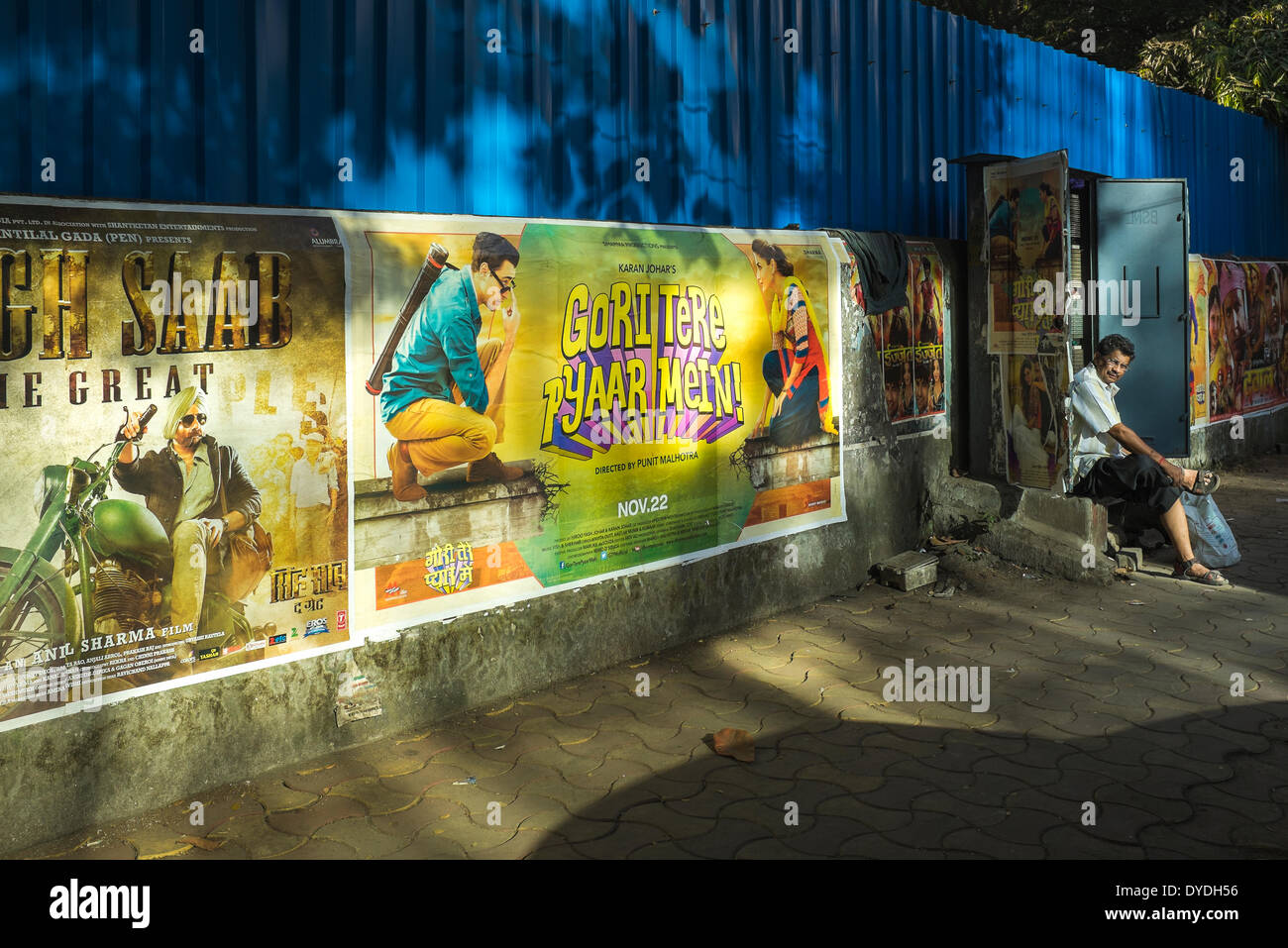 A telephone repairman takes break at an open junction box along a wall displaying Bollywood movie posters. Stock Photo