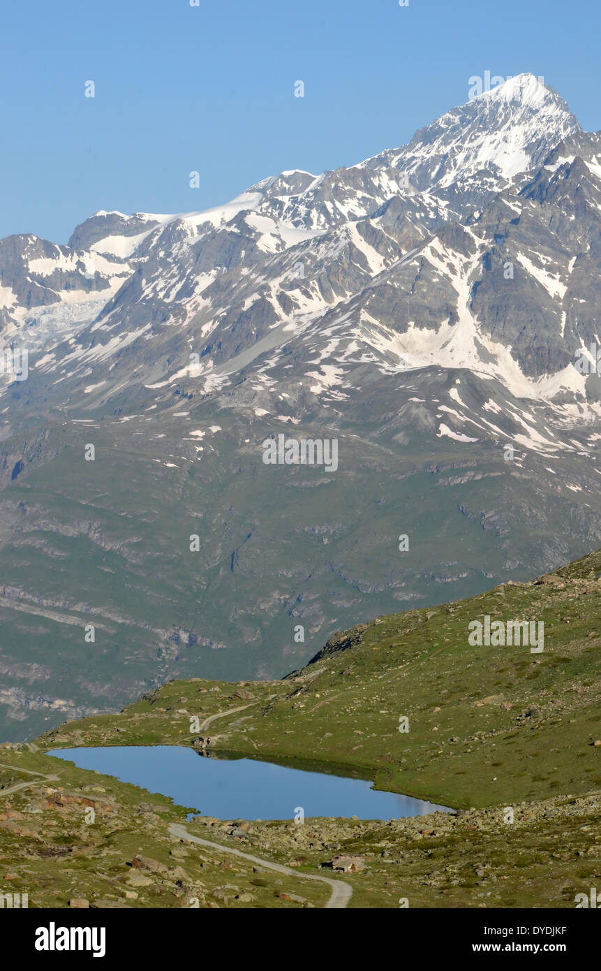 alps mountains snow lake water reflexion walkers hikers hiking path route leisure vacation sport exercise mountainous alpi - Stock Image
