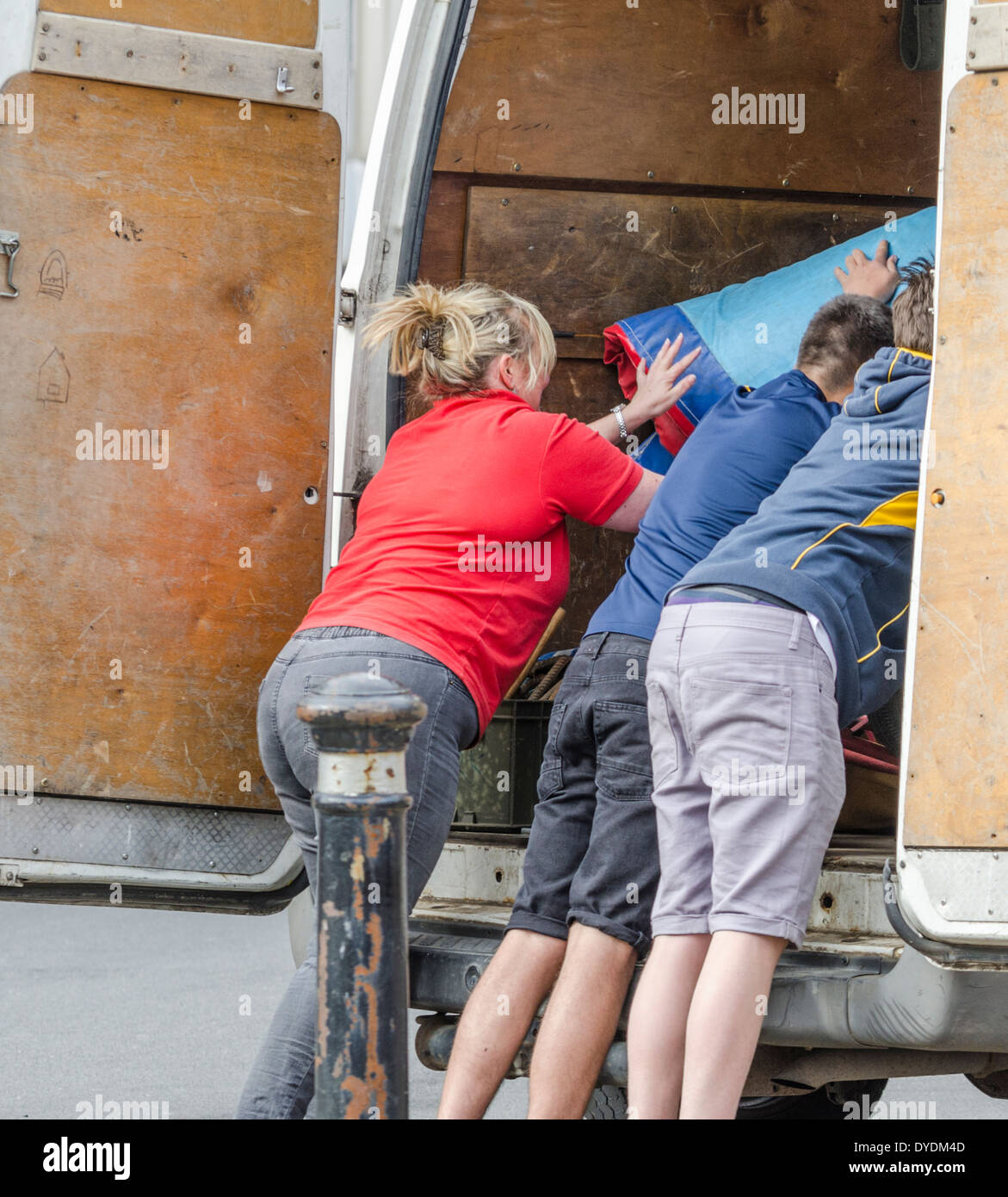 People loading items into the back of a van. - Stock Image