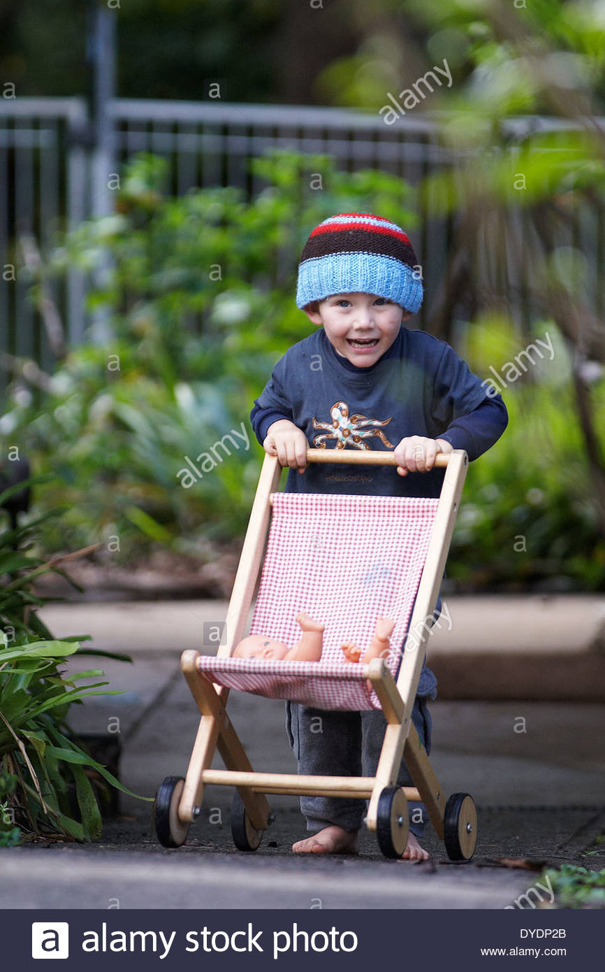 An excited small boy, in bare feet and a beanie, pushes a baby doll in a toy pram; along a path in the garden at a daycare centre in NSW, Australia. - Stock Image