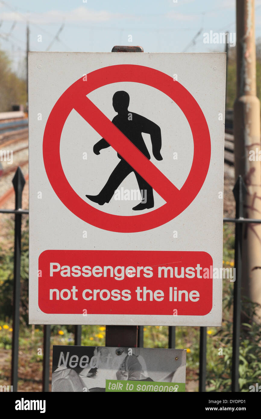 Railway track side warning sign (at Hanwell Station, West London, UK) advising passengers not to cross the track. - Stock Image