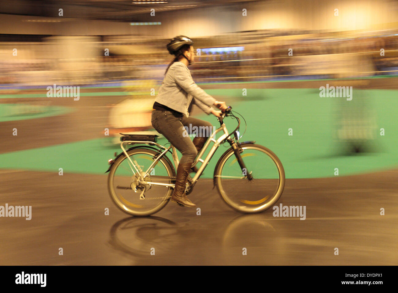 Woman on an electric bicycle moving at speed at the Gadget Show Live 2014 show at the NEC, near Birmingham, UK. - Stock Image